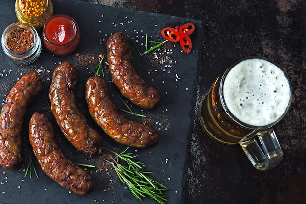 Grilled sausages on a dark stone board with a glass of beer