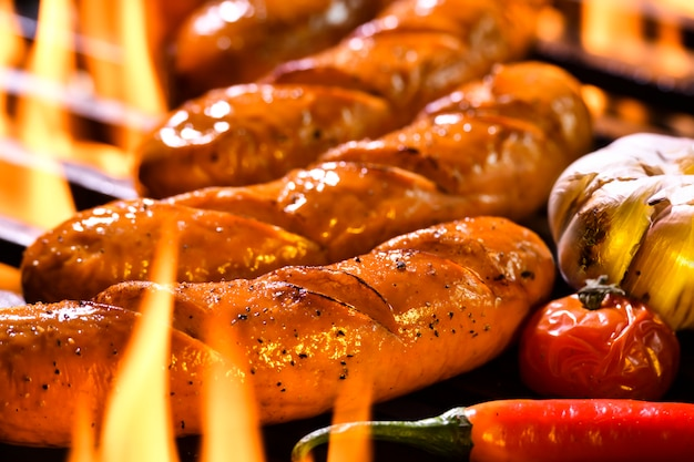 Grilled sausages on the flaming grill