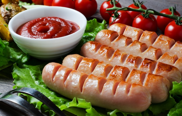 Grilled sausages on green lettuce leaves, tomato sauce, red cherry tomatoes on a branch. wooden dark background