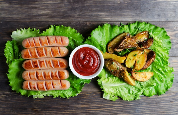 Grilled sausages on green lettuce leaves, tomato sauce, red cherry tomatoes on a branch.