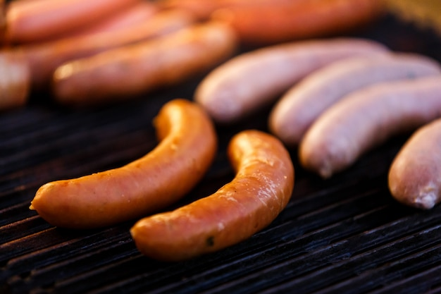 Grilled sausages on grill with smoke and flame in party night , selective focus