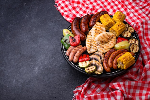 Grilled sausages, meat, and vegetables.
