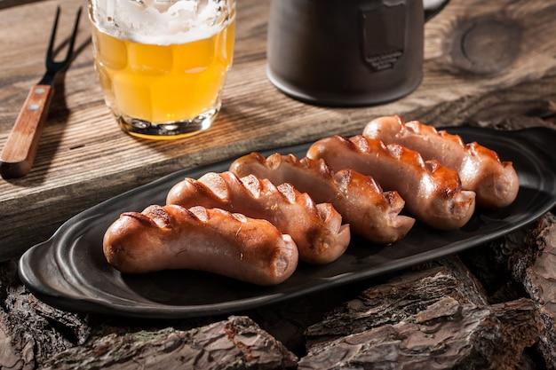 セラミックプレートのグリルソーセージと木製のテーブルのビールジョッキ