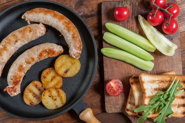 Колбаски гриль на сковороде, жареный картофель. сырые овощи на разделочной доске, деревянной поверхности. плоская планировка