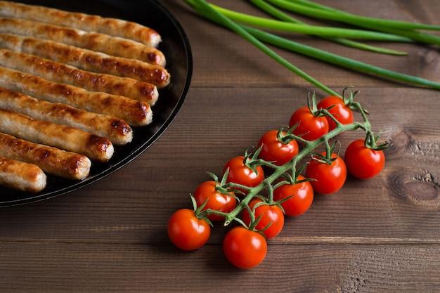 チェリートマトとネギと木製の茶色の背景のフライパンでグリルソーセージ