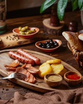 Жареные колбаски с жареным картофелем, горчицей и кетчупом