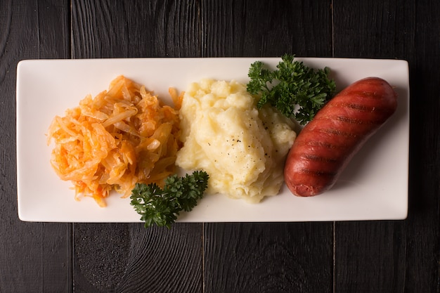 Grilled sausages and potatoes with glass of beer