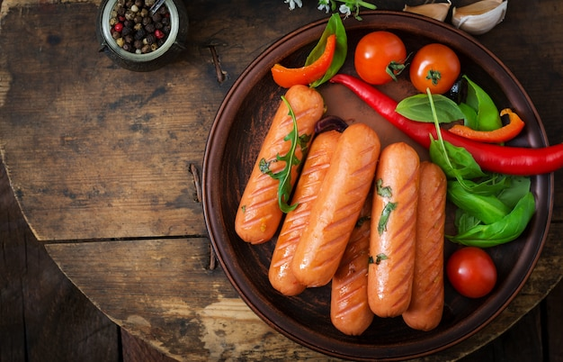 Grilled sausages and vegetables on a wooden background in rustic style. flat lay. top view