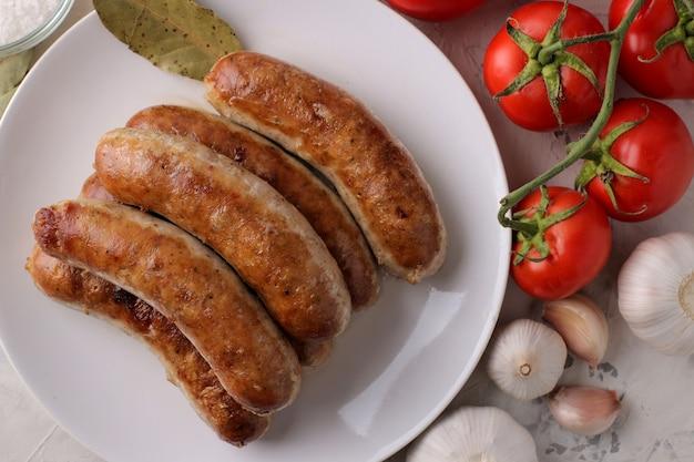 밝은 배경에 다양한 야채 토마토와 마늘을 곁들인 구운 소시지. 평면도
