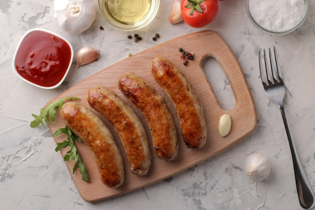 밝은 배경에 다양한 야채 토마토와 마늘, 붉은 소스, 향신료를 곁들인 구운 소시지. 평면도