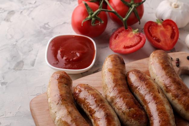 밝은 배경에 다양한 야채 토마토와 마늘, 붉은 소스, 향신료를 곁들인 구운 소시지.