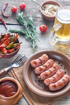 前菜とマグカップのビールのグリルソーセージ