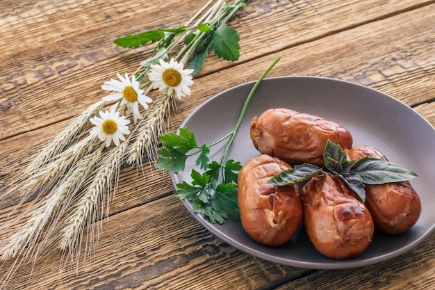 磁器皿にバジルとパセリを添えたソーセージのグリル。木の板に小麦とカモミールの花の耳を持つ上面図。