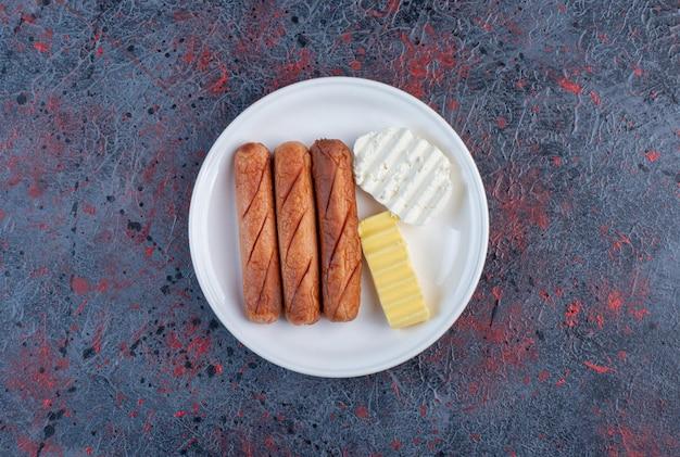 접시에 치즈 조각과 구운된 소시지입니다.