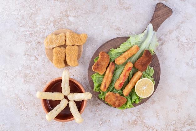 레몬과 함께 나무 판자에 양상추 조각에 치킨 너겟을 곁들인 구운 소시지.