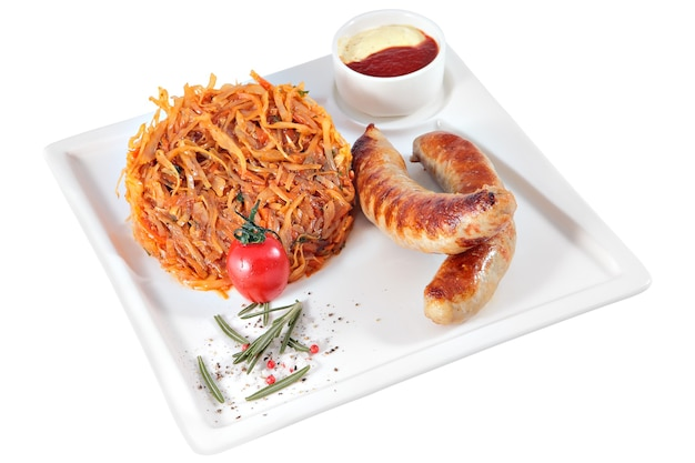 Жареные сосиски с гарниром из тушеной капусты и соусом на квадратной сервировочной тарелке, изолированной на белом фоне.