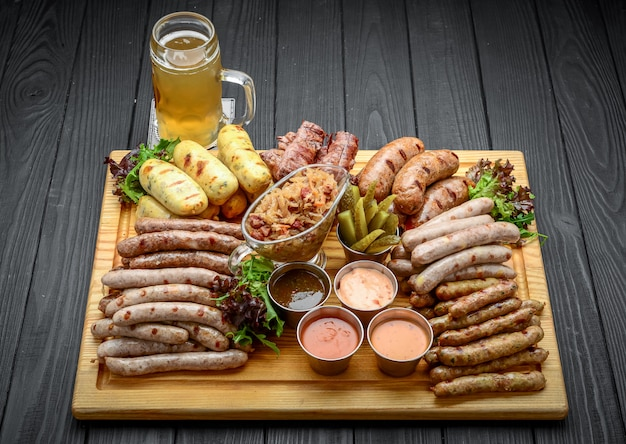 Grilled sausages with glass of beer on a wooden table