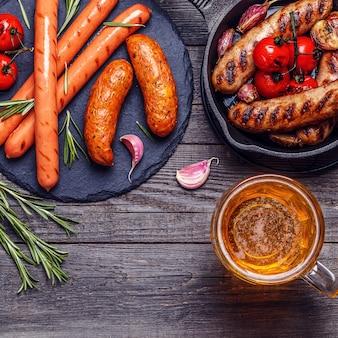 Жареные сосиски с бокалом пива на деревянном столе. вид сверху с копией пространства.