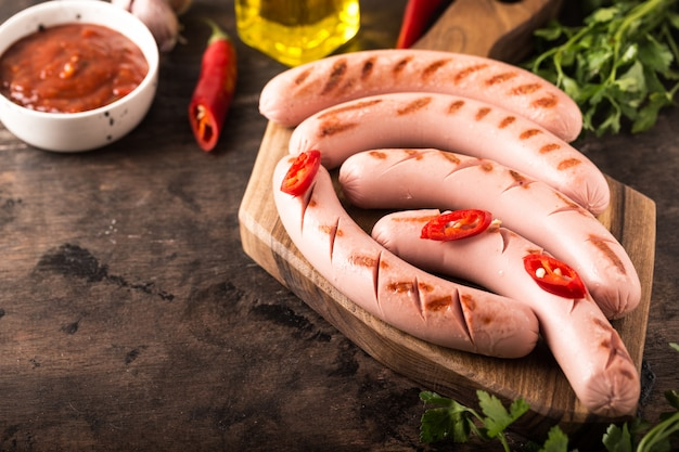 Grilled sausages with ketchup, herbs and hot chili peppers