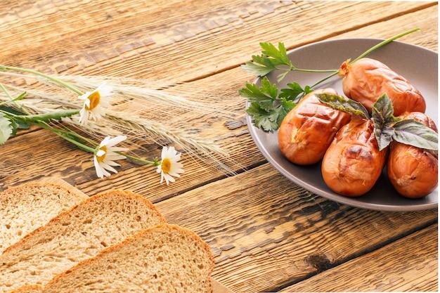 皿にパセリとバジル、カモミールの花、古い木の板に小麦の小穂を載せたグリルソーセージ。上面図