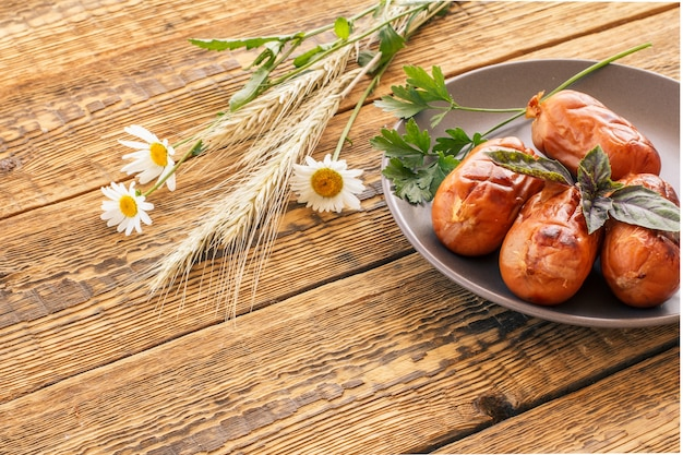 皿にパセリとバジル、カモミールの花、古い木の板に小麦の小穂を載せたグリルソーセージ。