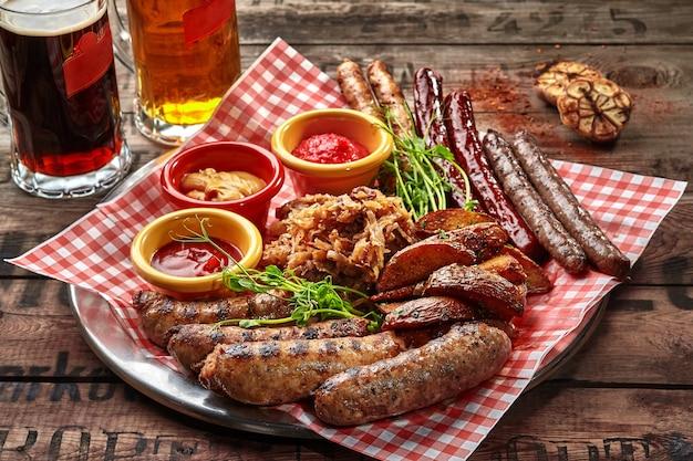 Колбаски гриль с картофельными дольками, тушеная капуста и соус в качестве закуски к пиву