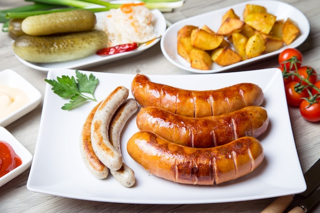 Колбаски гриль с картофелем, огурцами и квашеной капустой, с двумя соусами.
