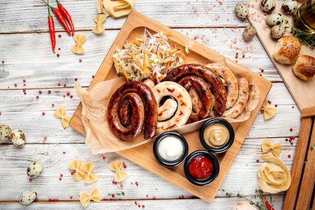 Колбаски гриль с квашеной капустой и соусами