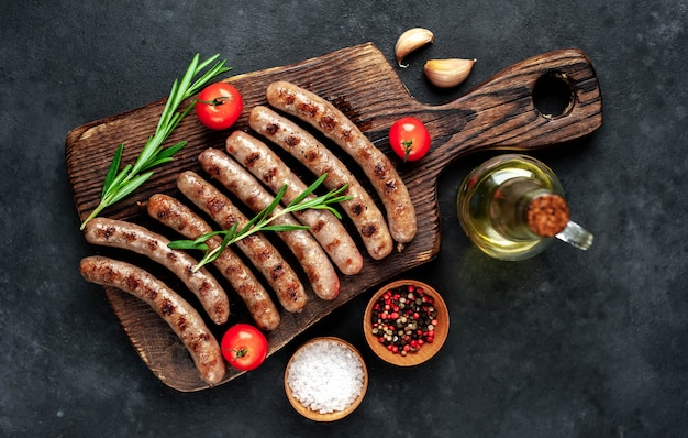 Grilled sausages with spices and rosemary on a stone table