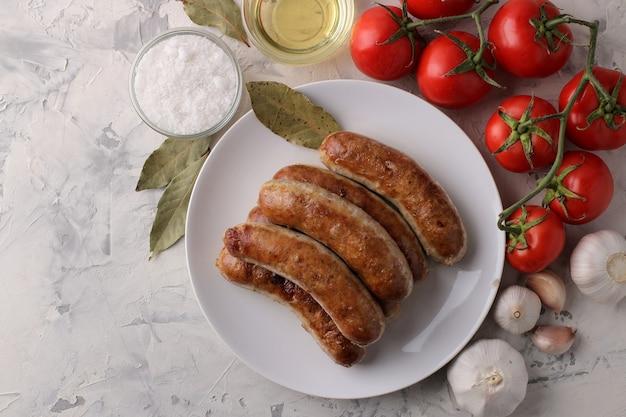 밝은 배경에 토마토, 해바라기 기름, 마늘을 곁들인 구운 소시지. 평면도