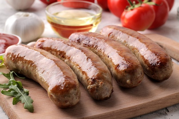 밝은 배경에 토마토, 해바라기 기름, 마늘을 곁들인 구운 소시지