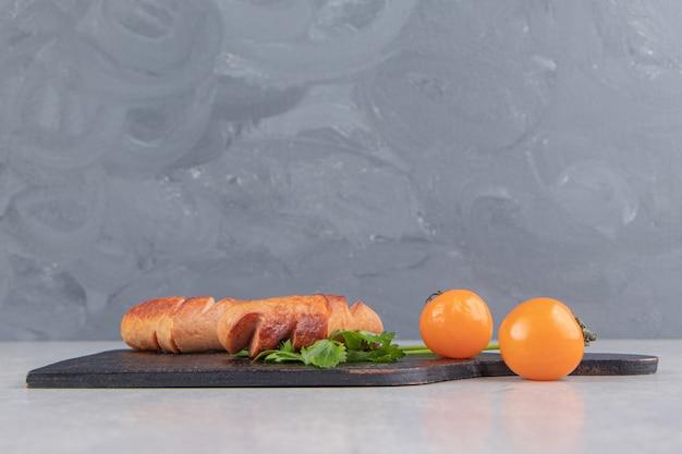 Salsicce alla griglia con pomodori su tavola di legno.