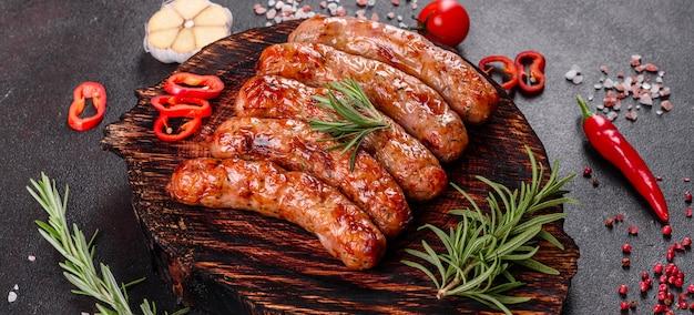 Колбаски гриль с овощами и специями на черном фоне