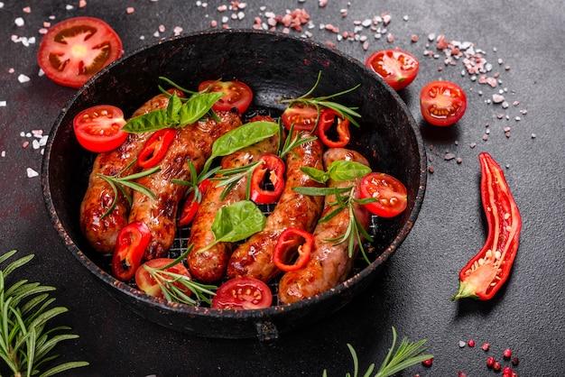 野菜と黒の背景にスパイスのグリルソーセージ