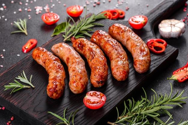 Колбаски гриль с овощами и специями на черном столе