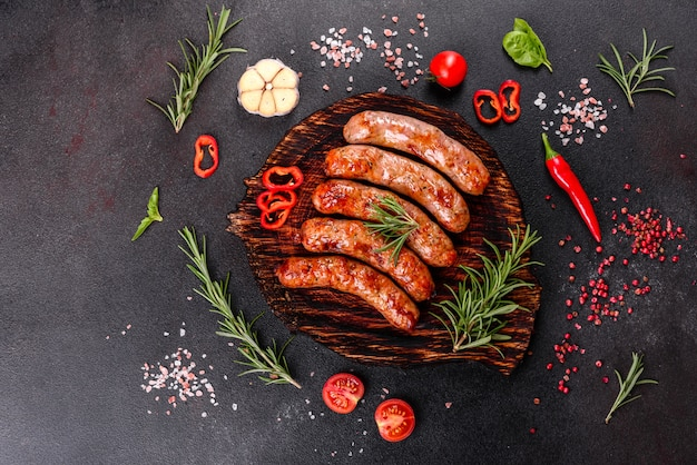 Grilled sausages with vegetables and spices on black