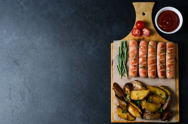 Grilled sausages on a wooden chopping board. fried potatoes, rosemary, tomatoes, tomato ketchup. unhealthy diet.