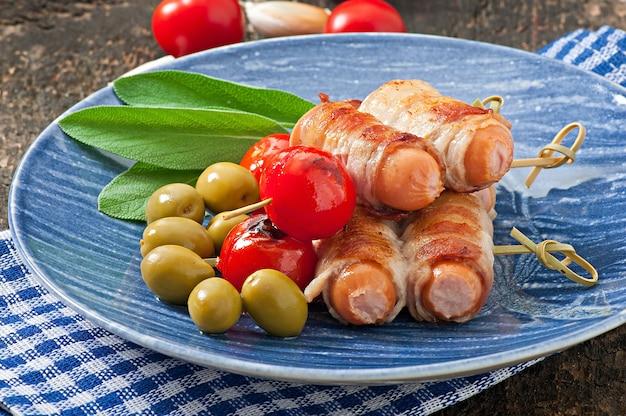 Колбаски гриль, завернутые в полоски бекона с помидорами и листьями шалфея