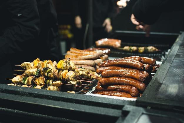 Жареные колбасы и шампуры на уличном продовольственном рынке