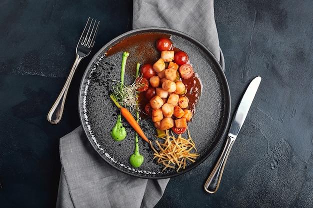Гребешки на гриле с овощами и соусом, красивая презентация от шеф-повара, фото еды, темный фон