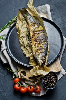 Grilled sea bass on kraft paper in a black plate.