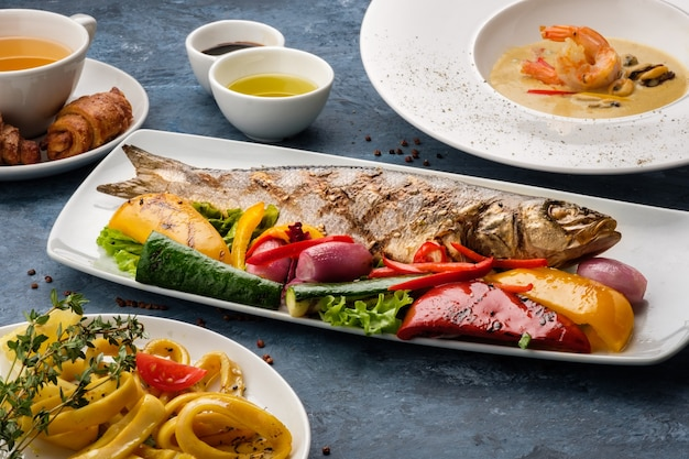 야채, 해산물 수프, 튀긴 오징어를 곁들인 구운 농어.