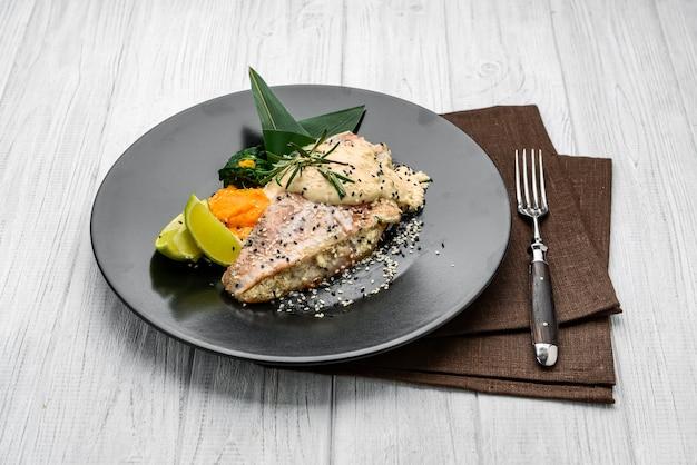 Морской окунь на гриле с белым соусом и лимоном. блюдо в ресторане
