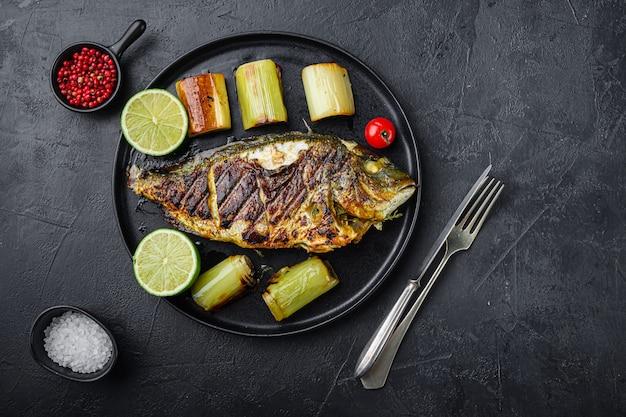 질감 된 검은 배경 위에 찐 부추와 검은 접시에 구운 도미 또는 황새 생선