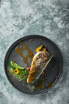 Grilled seabass with eggplant and lime. horizontal top view, top shot. copyspace, gray concrete marble , soft light. food fashion .