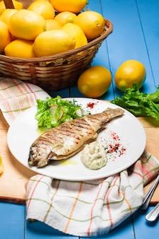 レモンと新鮮な野菜を添えたシーバスのグリル。素朴なサーブドディッシュ