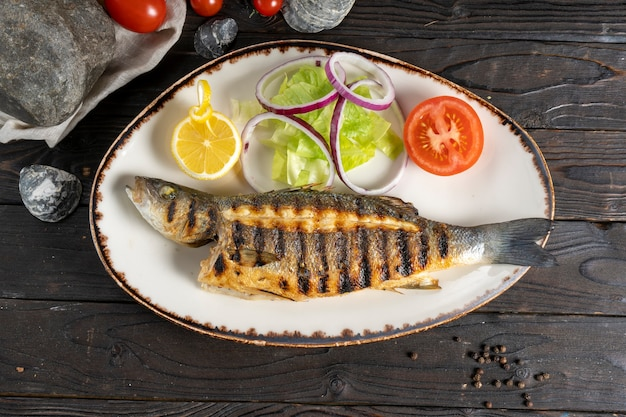 Grilled seabass with salad onions and tomatoes.