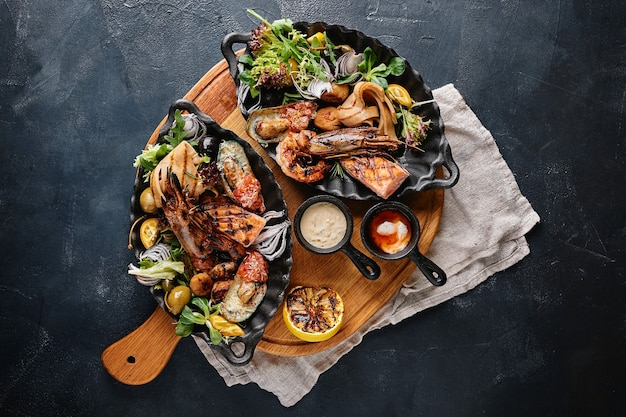 シーフードの盛り合わせのグリル。シーフードのグリルと野菜の盛り合わせ。ミックスバスタードのペッパーソースと野菜のグリル。青い背景。