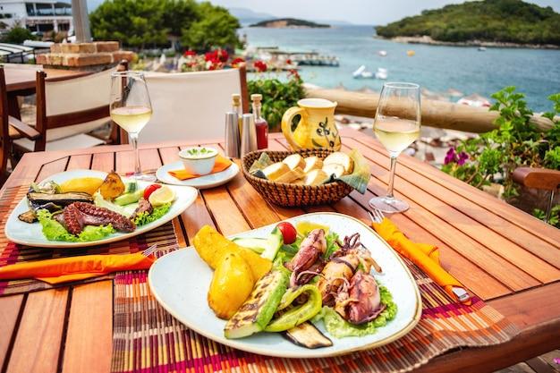 Морепродукты на гриле, фаршированные овощами и лимоном на столе