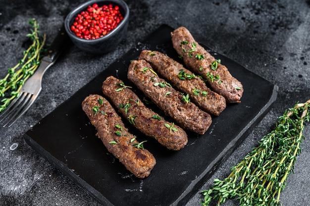 Шашлык на гриле мясные колбаски